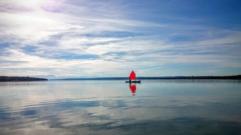 Kleines Segelboot mit roten Segeln auf dem Ammersee