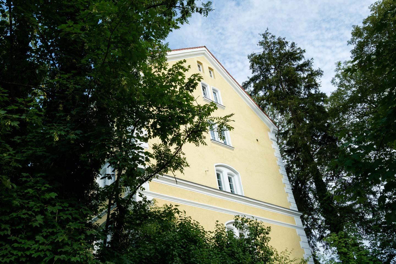Blick auf die in gelb gestrichene Außenfassade des LAB18. Das Gebäude ist umgeben von Bäumen und liegt etwas erhöht.