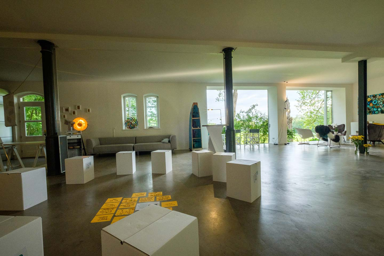 Blick auf Workshop- und Kreativbereich des LAB18 mit weißen Karton-Hockern im Stuhlkreis. In der Mitte des Stuhlkreis liegen gelbe Papiere auf dem Boden. Diese sind mit Workshop-Inhalten beschriftet. n