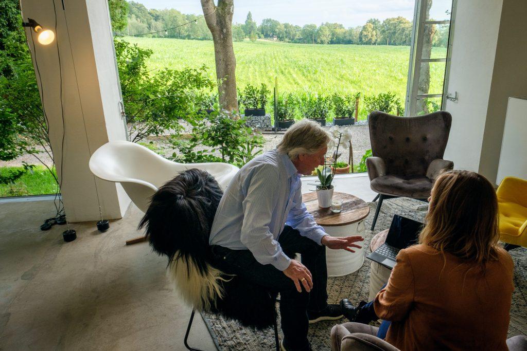 Wir sehen zwei Seminarteilnehmer im Chillout-Bereich mit verschiedenen Sesseln. Auf den runden Tischen steht ein Laptop. Die deckenhohen Fenster wurden komplett aufgeschoeben und geben den Blick frei auf die grüne Wiese.