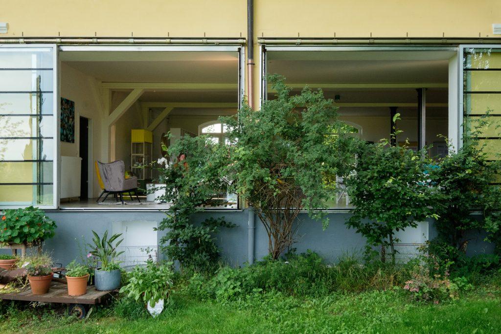 Blick von außen nach innen: Im Vordergrund sind die beiden wandhohe Fenster umrahmt mit grünen Büschen. Im Hintergrund ist die Inneneinrichtung des LAB18 zu sehen.