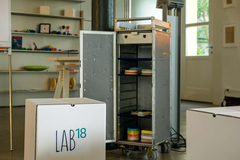 Detailansicht eines Flugzeug-Trolleys, der als Ablage für Workshop-Material wie Post-its dient. Im Vordergrund ist ein weißer Karton-Hocker mit der Aufschrift