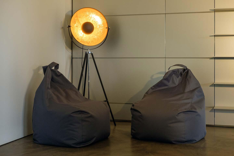 Blick auf zwei anthrazitfarbene Sitzsäcke in einer Ecke des Seminarraums. Dahinter befindet sich eine schwarze Stehlampe mit goldener Innenverkleidung.