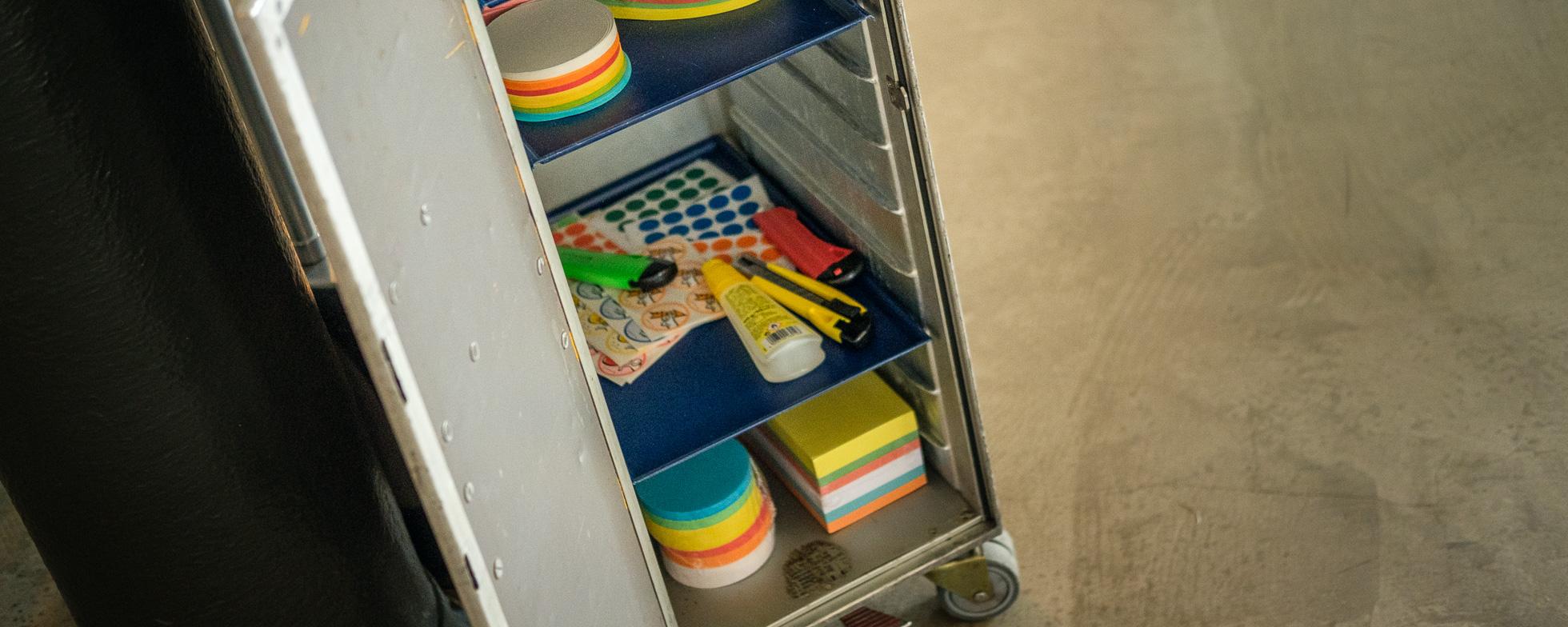 Detailblick in einen Trolley mit Workshop-Material wie Aufkleber, Post-its, Kleber und Schere.