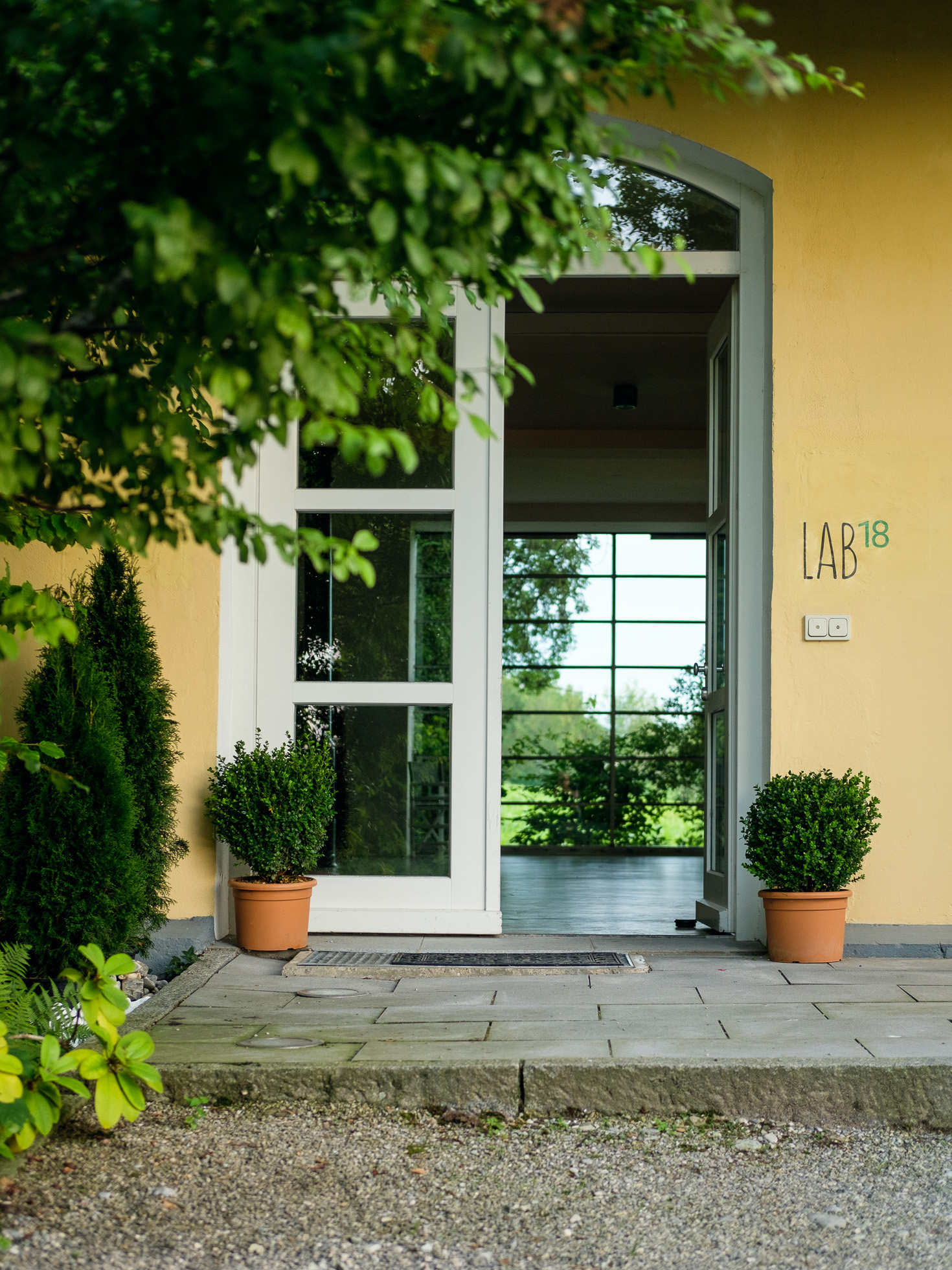 Außenaufnahme des Workshops-Raums LAB18 mit Eingangstür und gelber Außenfassade