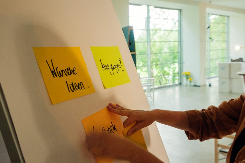 Workshop-Situation: Eine Seminarteilnehmerin bringt gerade ein Post-it auf dem Flipchart an