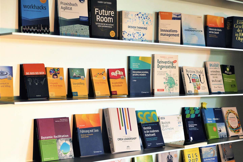Detailansicht des Bücherregals am linke Ende des Seminarraums mit Bücher zu den Themen